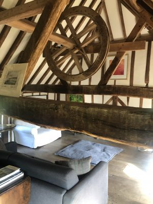 Wooden beams and wheel in the eaves of the Oast house lounge.