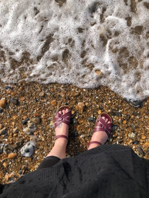 A photo of my feet on a beach next to an incoming wave. I am wearing a black dress and leggings, and some claret coloured saltwater sandals. It is a stony beach not sandy.